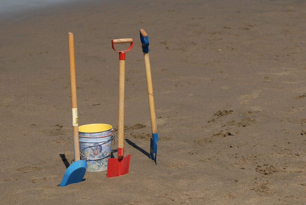Three beach shovels standing up in the sand next to a pail.