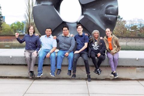 "The Agaric team sitting in front of Seattle's iconic ""black hole"" statue with our hands on each other's shoulders. Ben, in character, placing his hand on a non-existent person's shoulder next to him."