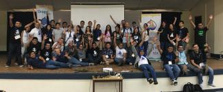 DrupalCamp Nicaragua attendees raising their hands in unison.