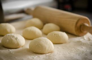 Seven fresh dough balls and a rolling pin.