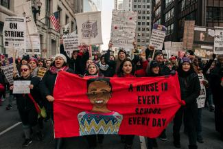 "Striking Chicago teachers marching in the street, carrying a banner ""A Nurse in Every School, Every Day."""