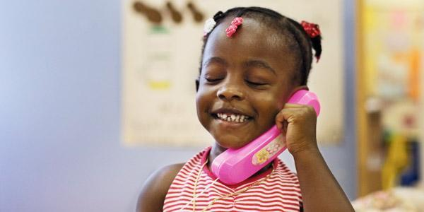 Child holding toy telephone.