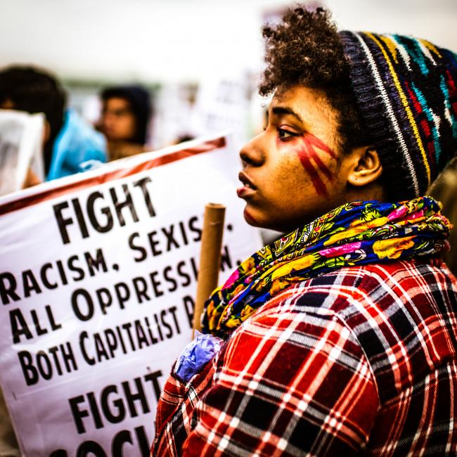 "A protester with a sign in the background that reads ""Fight Racism. Sexism. All Oppression."""